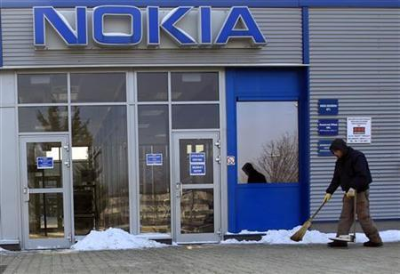 A man clears a road in front of the main gate at the Nokia phone assembly plant in Komarom, 85 km (52.8 miles) west of Budapest February 8, 2012. REUTERS/Laszlo Balogh/Files