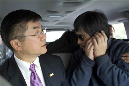 An handout photo from US Embassy Beijing Press office shows blind activist Chen Guangcheng (R) making a phone call as he is accompanied by U.S. Ambassador to China Gary Locke in a car on the way to a hospital in Beijing, May 2, 2012. REUTERS/US Embassy Beijing Press Office/Handout