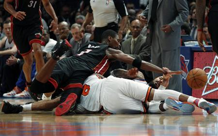 Miami Heat's Chris Bosh (top) dives over New York Knick's J.R. Smith for a loose ball during the second half of Game 3 of their NBA Eastern Conference basketball playoff series in New York, May 3, 2012. REUTERS/Mike Segar
