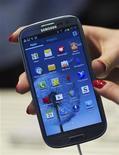 Женщина показывает новый смартфон Samsung Galaxy SIII на презентации в Лондоне, 3 мая 2012 года. Samsung Electronics представила новейший смартфон линейки Galaxy вечером в четверг в Лондоне, оснастив очередного конкурента iPhone более широким экраном и более мощным процессором. REUTERS/Ki Price