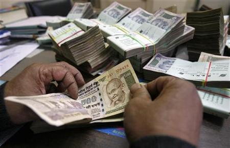 An employee counts rupee notes at a cash counter inside a bank in Agartala, December 31, 2010. REUTERS/Jayanta Dey/Files
