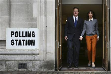 Britain's Prime Minister David Cameron walks from a polling station after voting in local elections with his wife Samantha (R) in central London May 3, 2012. REUTERS/Peter Macdiarmid/POOL
