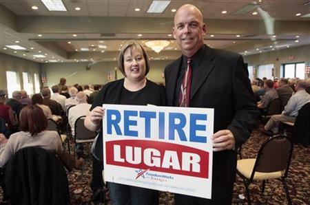 Monica Boyer (L) and Greg Fettig, co-founders of the Indiana Tea Party group ''Hoosier Patriots'', hold up a ''Retire Lugar'' lawn sign they brought with them from Indianapolis to a Tea Party gathering in Dewitt, Michigan November 12, 2011. REUTERS/Rebecca Cook