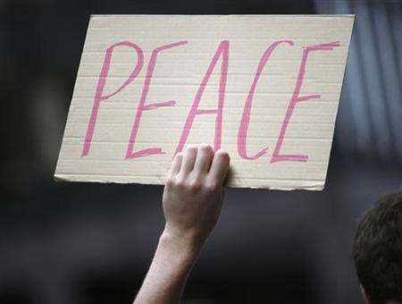 A demonstrator holds a peace sign during an anti-nuclear weapons protest rally and march in New York May 2, 2010. REUTERS/Chip East