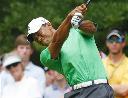 Tiger Woods grimaces as he hits his tee shot on the eighth hole during the second round of the Wells Fargo Championship PGA golf tournament in Charlotte, North Carolina May 4, 2012. REUTERS/Chris Keane