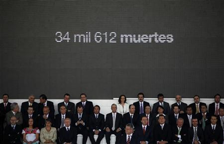 Representatives of Mexican major daily newspapers and the top television broadcasters, Televisa and TV Azteca, stand in front of a panel reading ''34,612 deaths'' during a meeting in Mexico City March 24, 2011. REUTERS/Jorge Dan Lopez