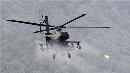 A U.S. AH-64 Apache helicopter fires a rocket during a joint live firing exercise between South Korea and the U.S. at the U.S. Army's Rodriguez Live Firing Range in Pocheon, about 46 km (28 miles) northeast of Seoul and about 15 km (9 miles) south of the demilitarized zone separating the two Koreas, September 1, 2011. REUTERS/Jo Yong-Hak