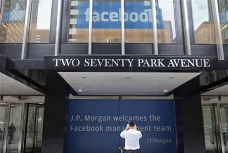 A man takes pictures of signs welcoming the IPO of Facebook outside the office of J.P. Morgan in New York City, May 4, 2012. REUTERS/Lee Celano
