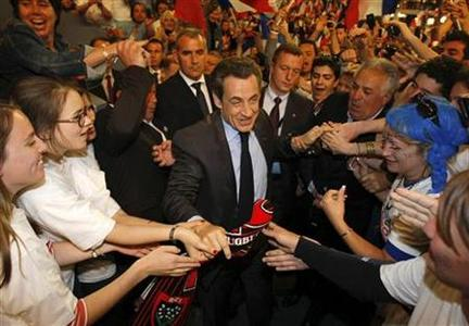 Supporters shake hands with France's President and UMP party candidate for the 2012 French presidential elections, Nicolas Sarkozy, as he arrives to attend a campaign political rally in Toulon, May 3, 2012. REUTERS/Claude Paris/Pool