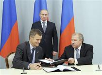 Russian Prime Minister and President-elect Vladimir Putin (C) looks on as Statoil's Chief Executive Helge Lund (L) and Rosneft President Eduard Khudainatov exchange documents during a signing ceremony at the Novo-Ogaryovo residence outside Moscow May 5, 2012. REUTERS/Yana Lapikova/RIA Novosti/Pool