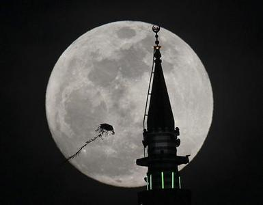 The full moon rises behind a mosque as a kite flies in Amman May 5, 2012. Saturday will see the rise of a full moon called the ''Super Moon'' when it arrives at its closest point to the Earth in 2012. REUTERS/Ali Jarekji