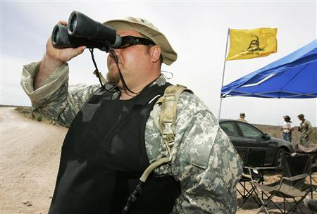 Minuteman Project volunteer Jason Todd ''JT'' Ready uses binoculars to scan for potential illegal immigrants while along the US/Mexico border west of Douglas, Arizona in this April 3, 2005 file photo. REUTERS/Fred Greaves/Files