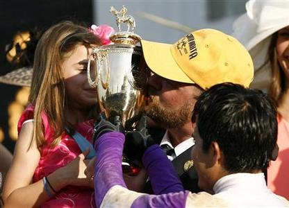 Jockey Mario Gutierrez holds the trophy as trainer Doug O'Neill kisses it after I'll Have Another won the 138th Kentucky Derby at Churchill Downs in Louisville, Kentucky, May 5, 2012. REUTERS/Matt Sullivan