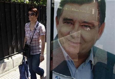 A woman walks next to a bus station with an election campaign poster showing Greece's far-right LAOS party leader George Karatzaferis in Athens May 5, 2012. REUTERS/John Kolesidis