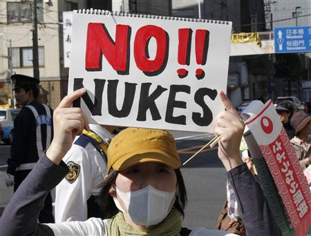 A protester holds a sign at a march appealing to the Japanese government to put an end to nuclear power in Tokyo May, 5, 2012. Japan shuts down its last working nuclear power reactor this weekend just over a year after a tsunami scarred the nation and if it survives the summer without major electricity shortages, producers fear the plants will stay offline for good. REUTERS/Kim Kyung-Hoon