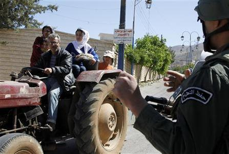 A family riding on a tractor pass a Syrian soldier at a checkpoint, during a field visit made by United Nations (U.N.) observers to the Madaya area, near Damascus May 6, 2012. REUTERS/Khaled al- Hariri