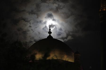 A full moon is seen behind the minaret of Mohamed Ali mosque, in Islamic Cairo, May 5, 2012. REUTERS/Asmaa Waguih