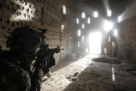 U.S. soldier Nicholas Dickhut from 5-20 infantry Regiment attached to 82nd Airborne points his rifle at a doorway after coming under fire by the Taliban while on patrol in Zharay district in Kandahar province, southern Afghanistan April 26, 2012. REUTERS/Baz Ratner