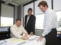 Norman Morgan (C) and Brent Sparks (R), principals at the architecture firm of HKS, Inc. talk with associate Marcus Budas (L) at the company's offices in Fort Worth, Texas, April 17, 2012. REUTERS/Tim Sharp