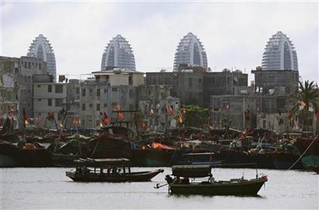 Fishermen navigate their boats past an area of old buildings, which are under demolition work in front of hotel buildings that are under construction on the man-made Fenghuang (Phoenix) island, at a fishing port in Sanya, Hainan province April 18, 2012. REUTERS/China Daily
