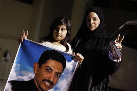 Arrested human rights activist Nabeel Rajab's wife Sumaya and daughter Malak hold a picture of jailed uprising leader Abdulhadi al-Khawaja during a protest demanding Rajab's release, outside their home in Bani Jamra, west of Manama May 6, 2012. REUTERS/Hamad I Mohammed
