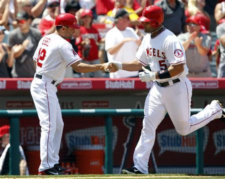 Los Angeles Angels third base coach Dino Ebel congratulates Angels' Albert Pujols (5) for hitting a two-run home run against the Toronto Blue Jays during the fifth inning of their MLB baseball game in Anaheim, California May 6, 2012. REUTERS/Alex Gallardo