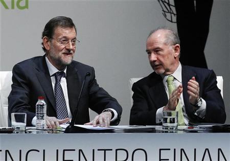 Spanish Prime Minister Mariano Rajoy (L) is applauded by President of Spanish bank Bankia, Rodrigo Rato, after talking at a conference in Madrid March 6, 2012. REUTERS/Andrea Comas