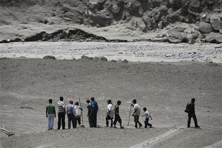 Locals look towards the bank of Seti River that used to be a small village, swiped away by a flash flood caused by an avalanche in the Annapurna mountain range on Saturday, in Kaski district May 6, 2012. REUTERS/Navesh Chitrakar