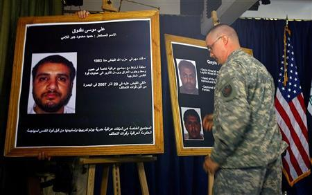 A U.S. solider shows a picture of Ali Mussa Daqduq (L) during a news conference at the heavily fortified Green Zone area in Baghdad July 2, 2007. REUTERS/Wathiq Khuzaie/Pool