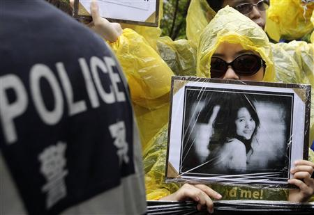 An activist holding a portrait of He Peirong, who helped blind Chinese activist Chen Guangcheng, shows her support while police officers attempt to stop the group in front of the American Institute in Taiwan (AIT), the de facto U.S. embassy in Taipei May 4, 2012. REUTERS/Pichi Chuang