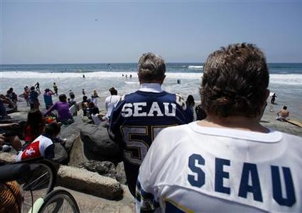 Some of the hundreds of friends and fans of ex-San Diego Chargers linebacker Junior Seau, who killed himself Wednesday with a shot to the chest, watch from the shoreline during a paddle-out memorial in front of his water front home in Oceanside, Californa May 6, 2012. REUTERS/Mike Blake