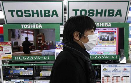 A man walks past Toshiba Corp's Regza liquid-crystal display (LCD) televisions at an electronic store in Tokyo January 31, 2012. REUTERS/Toru Hanai