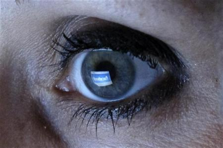 An illustration picture shows a woman looking at the Facebook website on a computer in Munich February 2, 2012. REUTERS/Michael Dalder