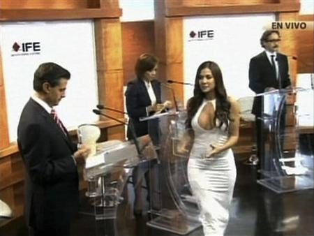 Former Playboy model and presidential debate assistant Julia Orayen (white) hands out cards to the four candidates during a televised debate at the Federal Electoral Institute in this handout still image taken from video, in Mexico City, May 7, 2012. REUTERS/Instituto Federal Electoral/Handout/ via Reuters TV