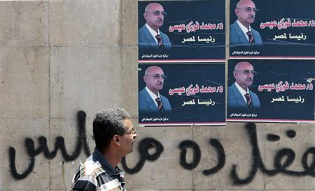 A man walks past campaign posters of presidential candidate Mohamed Fawzi Eissa in Cairo May 7, 2012. REUTERS/Amr Abdallah Dalsh