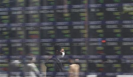 A man wearing a mask is reflected on a stock quotation board outside a brokerage in Tokyo April 24, 2012. REUTERS/Toru Hanai