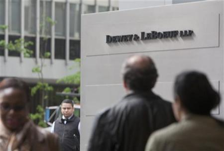 People walk past a sign outside the law firm Dewey & LeBoeuf in New York City May 1, 2012. REUTERS/Lee Celano
