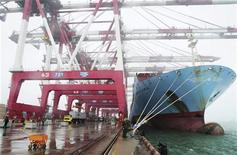 Employees unload containers from a cargo ship as frontier inspection soldiers (C) stand guard at Qingdao port during a rainy day in Qingdao, Shandong province April 10, 2012. REUTERS/China Daily