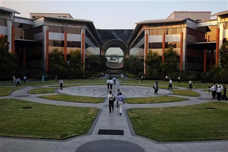 Employees walk in front of a building dubbed the ''washing machine'', a well-known landmark built by Infosys at the Electronics City IT district in Bangalore, February 28, 2012. REUTERS/Vivek Prakash