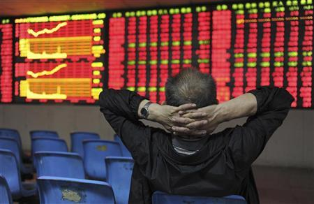 An investor places his hands on the back of his head in front of an electronic board showing stock information at a brokerage house in Hefei, Anhui province May 2, 2012. REUTERS/Stringer