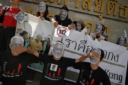 Protesters gather outside the Criminal Court in Bangkok December 9, 2011. Protesters wore masks and hold pictures of Amphon Tangnoppaku, dubbed ''Uncle SMS'', for 112 minutes outside the court protesting after he was jailed for 20 years last month for sending text messages deemed to have disparaged Thailand's Queen Sirikit. Lese-majeste, or the offence of insulting the king, queen, crown prince or regent, is article number 112 in Thailand's Criminal Code. REUTERS/Damir Sagolj
