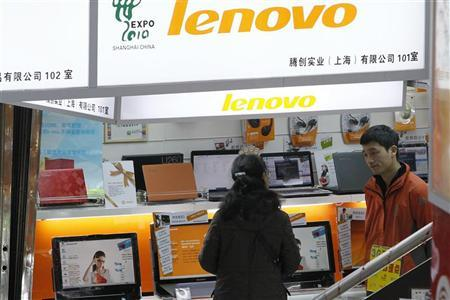 A customer (L) talks to a salesperson about a new laptop at a Lenovo shop in Shanghai. REUTERS/Aly Song