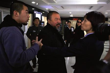 Dissident Chinese artist Ai Weiwei (C) argues with a tax official as he arrives with his wife Lu Qing (2nd R) and assistants at the Beijing government tax bureau November 16, 2011. REUTERS/David Gray