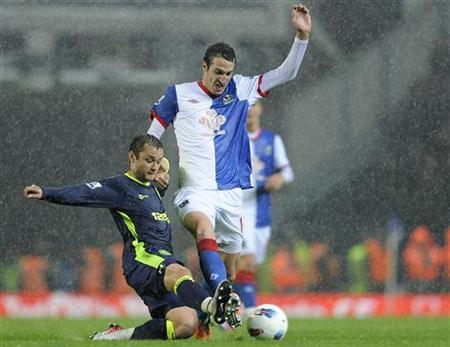 Blackburn Rover's Radosav Petrovic (R) challenges Wigan Athletic's Shaun Maloney during their English Premier League soccer match in Blackburn, northern England May 7, 2012. REUTERS/Nigel Roddis