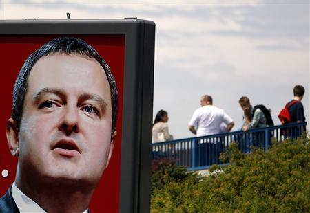 People wait for a bus near a pre-election billboard of the Socialist party leader Ivica Dacic in Belgrade May 7, 2012. REUTERS/Marko Djurica