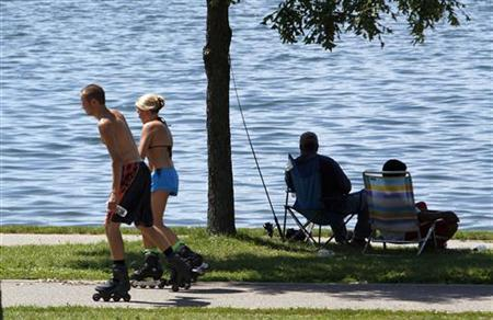 Rollerbladers skate past fishermen sitting in the shade as they seek relief from high temperatures by Lake Calhoun in Minneapolis, July 18, 2011. REUTERS/Eric Miller