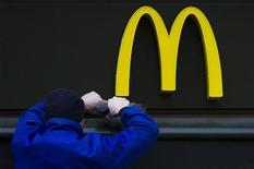 A worker drills a hole underneath the McDonald's brand sign at a store of the global fast food chain in Berlin February 15, 2012. REUTERS/Thomas Peter