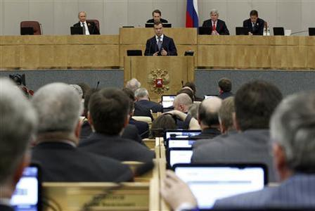 Russia's former President and prime ministerial candidate Dmitry Medvedev (facing camera, C) speaks, while President Vladimir Putin (facing camera, L) listens, during a session of the Russian State Duma in Moscow May 8, 2012. REUTERS/Maxim Shemetov