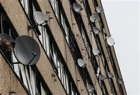 Satellite dishes are seen on the side of a block of flats in south London July 29, 2011. REUTERS/Luke MacGregor/Files