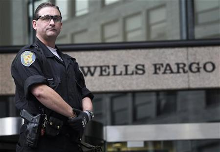 A Seattle police officer guards the Wells Fargo building during May Day demonstrations that went violent in downtown Seattle May 1, 2012. REUTERS/Anthony Bolante